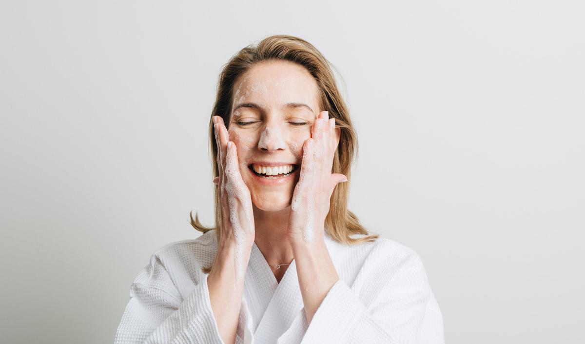 Kvinna som tvättar sig i ansiktet
